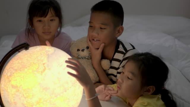 asiatiska barns grop lära sig om geografi på sovrummet. - bordsjordglob bildbanksvideor och videomaterial från bakom kulisserna