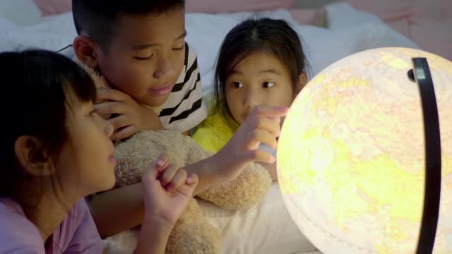 asiatiska barn grupp lära sig om geografi på sovrummet. - bordsjordglob bildbanksvideor och videomaterial från bakom kulisserna