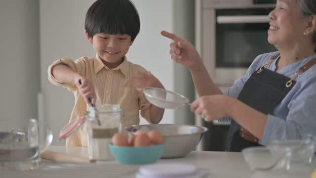 asian chinese 6 years old boy helping his grandmother preparing food with flour baking at kitchen counter together