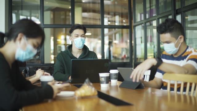 カフェでアジアの中国人が食べ物を楽しみ、新しい通常のフェイスマスクを着用して週末を冷やす - カフェ文化点の映像素材/bロール