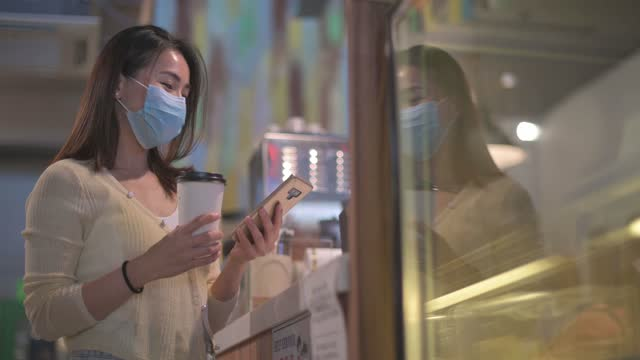 Asian chinese beautiful woman making payment through contacless payment using her mobile app at the cashier with face mask in cafe