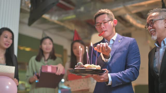 asian chinese business man lighting up birthday candle surprise office birthday party celebration