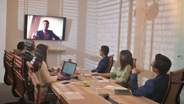 asian chinese business meeting in conference room with television screen presentation