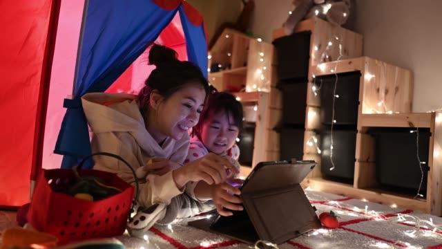 아시아 중국 아이 재생 에 이 놀이 에 텐트 에 이 텐트 사용 디지털 태블릿 누워 와 그녀의 어머니 - 놀이 방 스톡 비디오 및 b-롤 화면