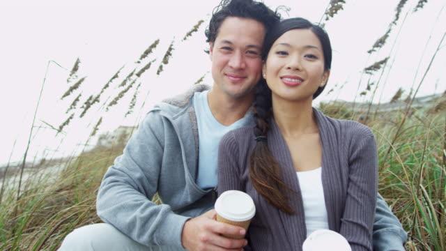 vidéos et rushes de chinois asiatiques couple jouissant plage d'automne boisson chaude - évasion du réel