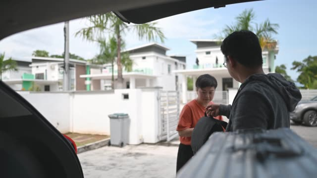 asian chinese couple getting ready loading luggage in their SUV going for vacation