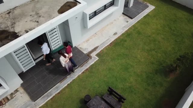 asian chinese couple receiving house keys from real estate agent outside new house