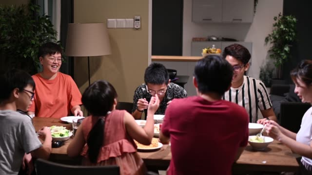 asian chinese families and friends having night dinner gathering at home with traditional chinese steamboat dishes