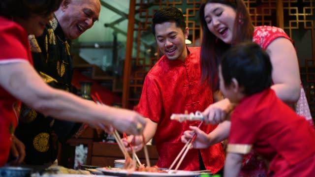 亞洲中國家庭中國新年團圓晚餐有傳統菜肴生魚勞唱。 - chinese new year 個影片檔及 b 捲影像