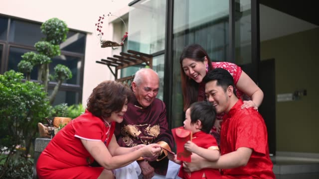 asian chinese family senior grandparent giving red packet ang pao to grandson after chinese new year reunion dinner having traditional dishes raw fish lau sang