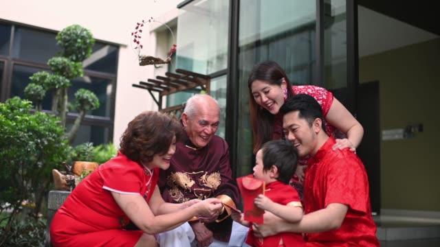 亞洲中國家庭高級祖父母給紅包安寶孫子後, 中國新年團聚晚餐有傳統菜肴生魚勞唱。 - chinese new year 個影片檔及 b 捲影像