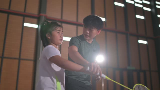 asian chinese female badminton trainer teaching her student in badminton court