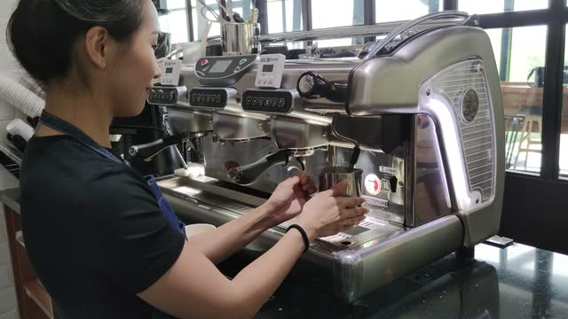 Asian Chinese female barista making coffee with coffee machine in the cafe