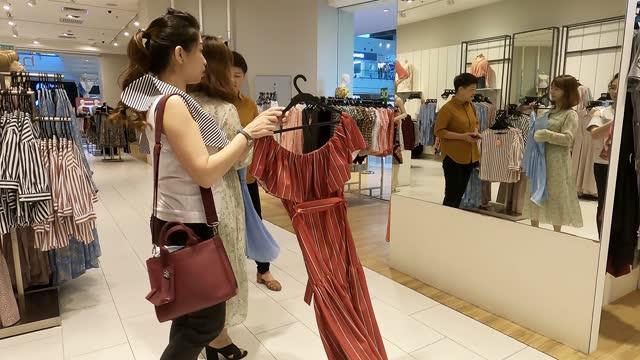stockvideo's en b-roll-footage met aziatische chinese wijfje dat kleren bij kledingopslag kiest die spiegel bekijkt - aziatische etniciteit
