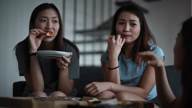 3 asian chinese female friends having pizza for lunch in their living room bonding time