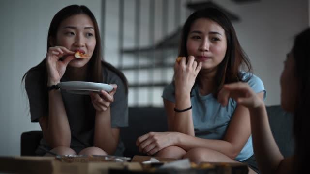 3アジアの中国の女性の友人は、彼らのリビングルームのボンディング時間に昼食のためにピザを持っています - おやつ点の映像素材/bロール