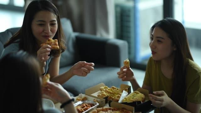 3 amiche cinesi asiatiche che hanno pizza per pranzo nel loro soggiorno - amicizia tra donne video stock e b–roll