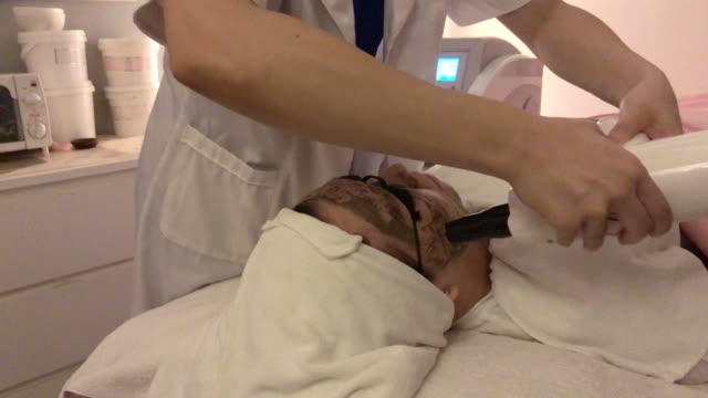 Asian chinese female receiving laser facial treatment at facial beauty salon