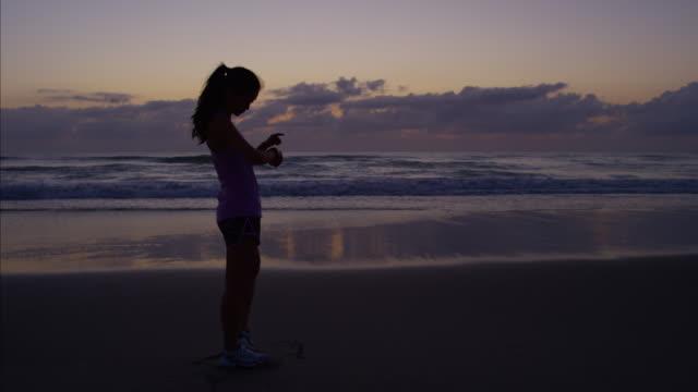 kumsalda güneş doğarken koşu asyalı çinli kız - dijital yerli stok videoları ve detay görüntü çekimi