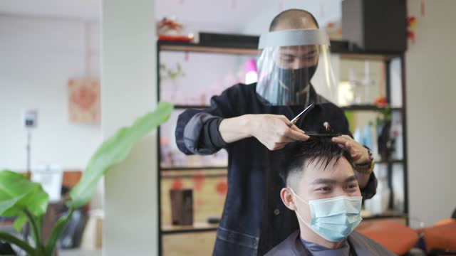 asian chinese hairstylist with protective workwear cutting hair for his customer in hair saloon asian chinese hairstylist with protective workwear cutting hair for his customer in hair saloon hairstyle stock videos & royalty-free footage