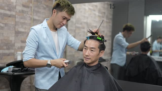 Asian Chinese male hairdresser using hair clipper shave man's hair in Saloon. Barber shop.