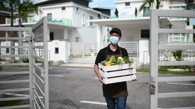 asian chinese male home delivery on food vegetable to his customer