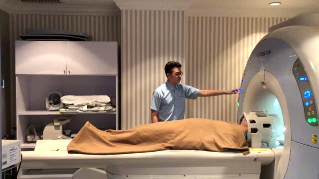 病院でmriスキャンを介して健康診断を受けている彼の成人男性患者を助けるアジアの中国の男性看護師 - mri検査点の映像素材/bロール