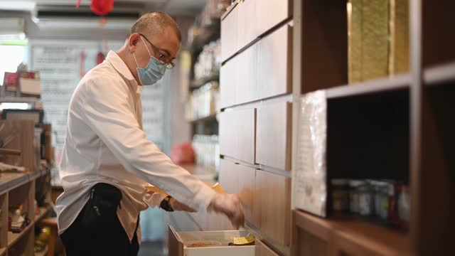 Asian chinese male pharmacist picking and packed chinese herbs medicine from the tray at traditional chinese herbal medicine shop