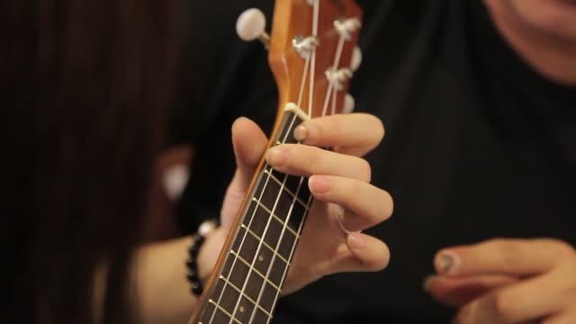 아시아 중국 남성 ukelele 교사 가르치는 그의 파트너 에 배울 기타 에 홈 - 연습하기 스톡 비디오 및 b-롤 화면