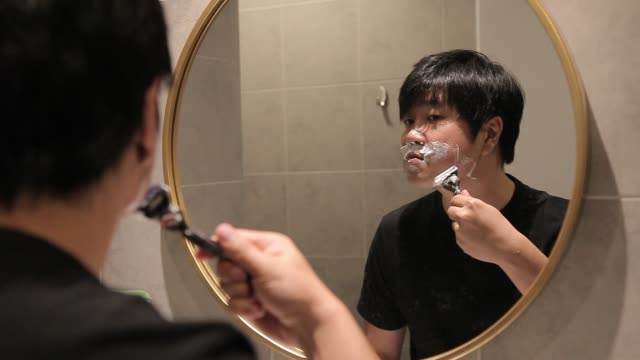 asian chinese man shaving at home - lama oggetto creato dall'uomo video stock e b–roll