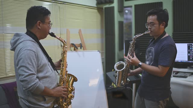 Asian chinese mid adult man learning music instrument playing saxophone from his instructor in music studio