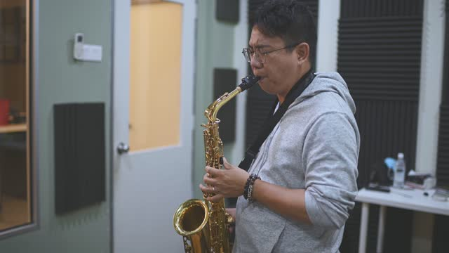 Asian chinese mid adult man learning music instrument playing saxophone in music studio class