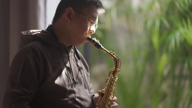 asian chinese mid adult man practicing saxophone at living room