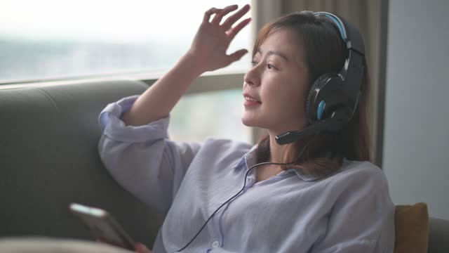 Asian chinese mid adult woman listening music with headphones on sofa in living room during sunset