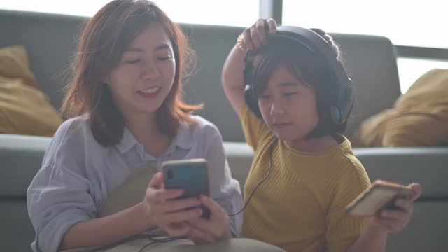 asian chinese mother enjoying weekend leisure time with her daughter listening music with mobile phone