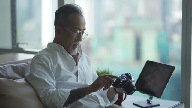 asian chinese retired senior man relaxing at living room looking at his camera and digital tablet