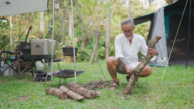 Asian chinese senior man cutting wood getting ready to setup campfire at camp