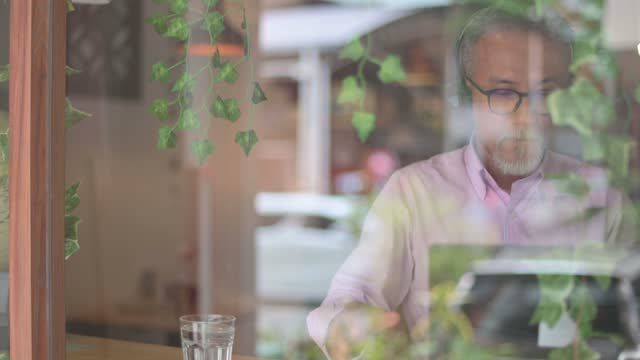 asian chinese senior man having discussion with his colleague via online virtual meeting in a cafe