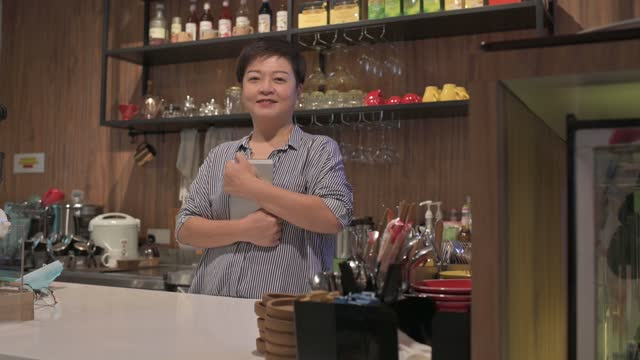 asian chinese small business owner at kitchen counter smiling looking