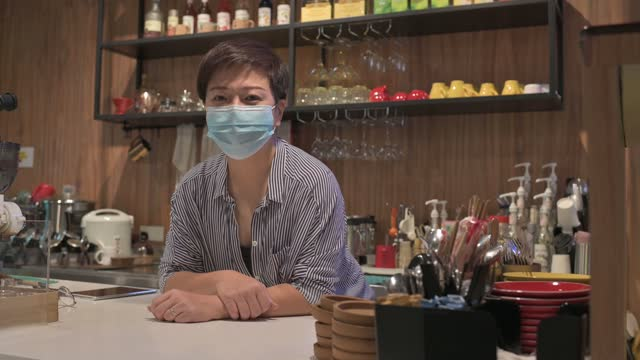 asian chinese small business owner with face mask at kitchen counter smiling looking