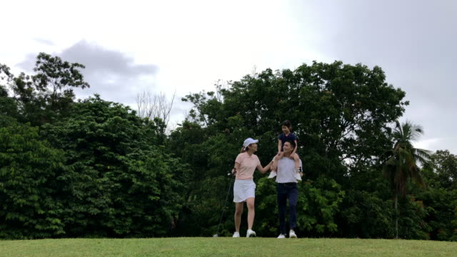 Asian chinese smiling young couple golfer bonding with daughter on the golf course