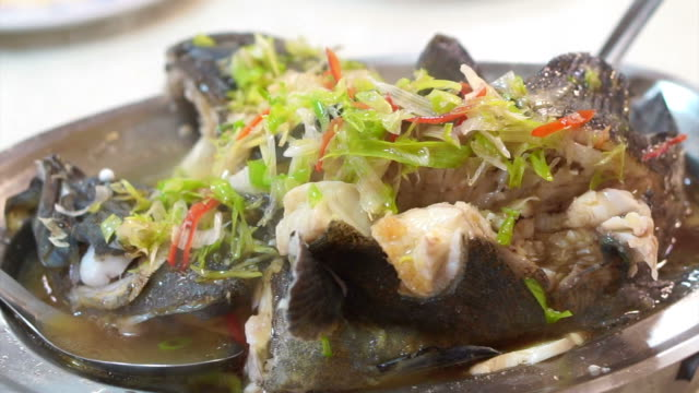 vídeos de stock e filmes b-roll de asian chinese style whole fish steamed with soy sauce and spring onion topping - inteiro