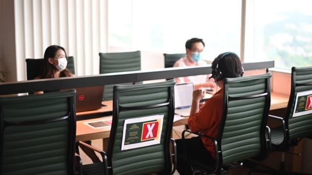vídeos de stock, filmes e b-roll de asiático trabalhador de colarinho branco chinês de volta ao trabalho após quarentena com novo sop e precauções de segurança de prevenção de doenças de distanciamento social - distante