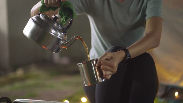 donna asiatica cinese versando verde acqua caldo dal bollitore e bevendo davanti al campeggio tenda nel cortile della loro casa attività del fine settimana di soggiorno - disintossicazione video stock e b–roll