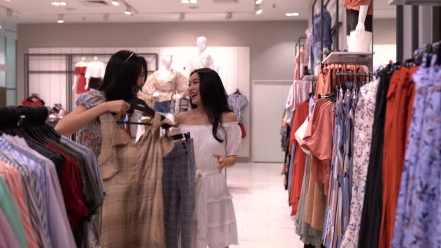 asian chinese women shopping and browsing at clothing retail store