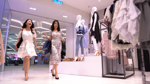 stockvideo's en b-roll-footage met aziatische chinese vrouwen die in kledingopslag lopen om te winkelen - aziatische etniciteit
