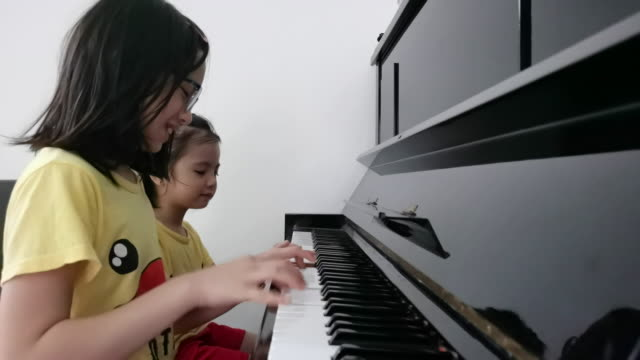 2 asian chinese young girl playing piano for fun at home together