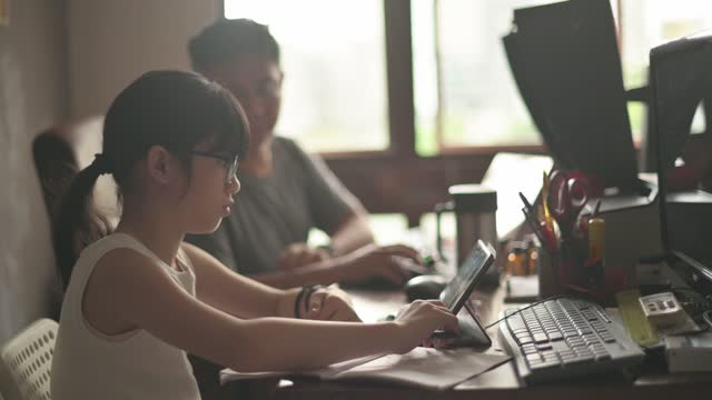 asian chinese young girl studying at home in her father's home office attending online class