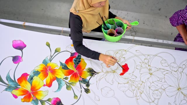 asiatiska kollegor arbetar tillsammans i en batik-workshop - anständig klädsel bildbanksvideor och videomaterial från bakom kulisserna