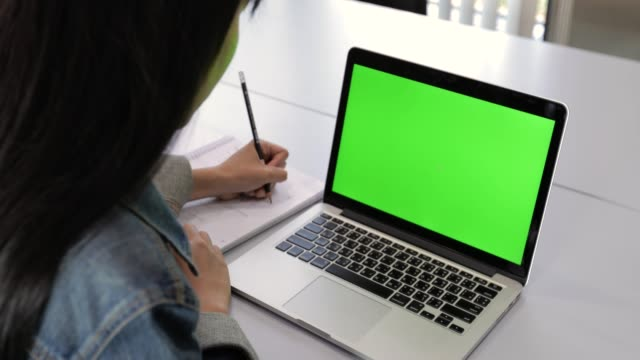 asian college students looking at laptop with green screen - studente video stock e b–roll